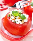 Tomato filled with feta cheese, garnished with pine seeds and basil