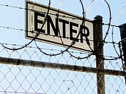 'ENTER' sign seen through barbed wire fence