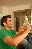 Young man with black hair laughing at a golden_colored sneaker, selective focus