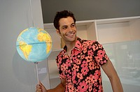 Young man in a Hawaiian shirt touching a globe_lamp, selective focus
