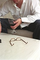 Man holding a Glass of Red Wine and Glasses laying on a Table
