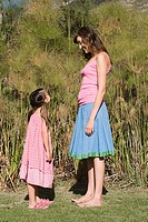 Mother and daughter standing face to face and smiling (thumbnail)