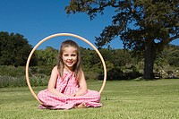 Little girl sitting inside hula hoop in park