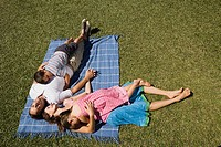 Family lying on picnic blanket