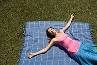 Woman lying on picnic blanket with arms outstretched