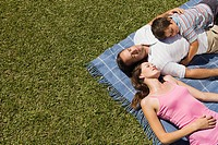 Couple and young son lying on picnic blanket