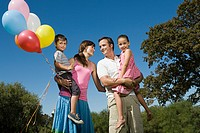 Family standing outside holding balloons