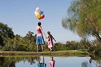 Mother and daughter standing hand in hand next to lake holding balloons