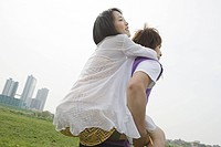 Young man giving girlfriend piggyback