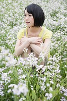 Young woman sitting in field of flowers