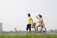 Young man walking and young woman on bicycle