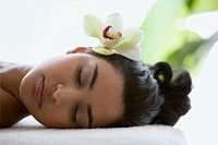Young woman on massage table with orchid flower in hair