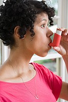 Woman taking asthma inhaler