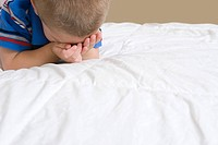 Little boy crying on bed