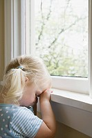 Sad little girl by window