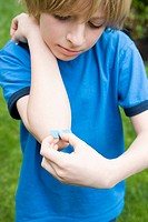 Boy putting plaster on elbow