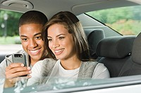 Young couple using a cellular telephone in car