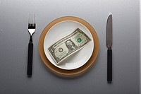 american one dollar on plate with fork and knife