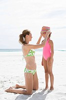 Woman adjusting young daughters sunhat at the beach