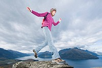 Young Woman Leaping Across Rocks