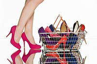 Legs of woman and shopping basket full of shoes