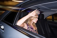 Woman with hand raised to car window