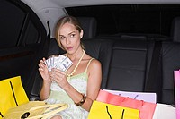 Woman with shopping bags and cash in a car
