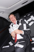 Wealthy businessman celebrating in a car