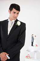 Worried looking groom with wedding cake