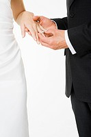 Groom placing a ring on brides finger