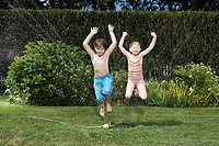 Children jumping in sprinkler