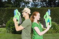 Couple standing back to back with water pistols