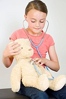 Girl with teddy bear and stethoscope