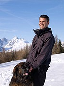 man with dog up on snowy mountain