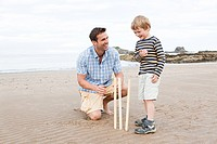 Father and son on beach with cricket stumps (thumbnail)