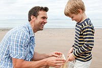 Father and son on beach with cricket stumps