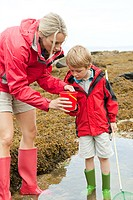 Mother and son looking in rock pool