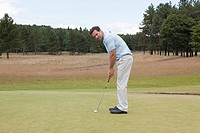 Male golfer putting (thumbnail)