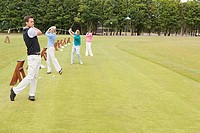 Four golfers on the driving range