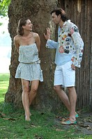 Young couple in summer outfit standing under a tree