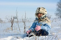 Girl in the fur_cap sitting in snow