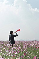 businessman standing amongst cosmos flowers in field holding megaphone