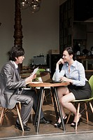 Two Business Colleagues Discussing an Application Form at a Table in cafe, moolrae dong, youngdeungpo_gu, seoul, south korea