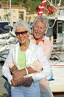 senior couple on holiday strolling at harbour area