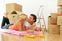 Happy young couple celebrate with champagne and fast food into new home