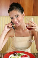 young woman drinking red wine in a restaurant and using cellphone