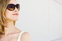 Woman wearing sunglasses, looking away, portrait