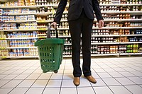 Shopper with shopping basket standing in supermarket aisle (thumbnail)