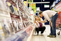 Couple selecting cell phone from store display (thumbnail)