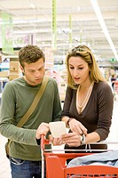 Couple with shopping cart reviewing receipt